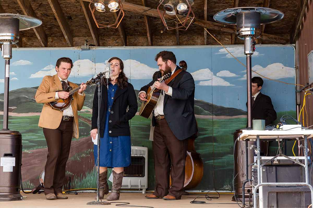 On an outdoor stage flanked by heaters, a four-piece band perform: a woman in a blue dress and black jacket singing, a man on mandolin, a man on guitar, and someone hidden playing upright bass. The backdrop is a landscape mural with rolling green hills, blue skies, and fluffy white clouds.