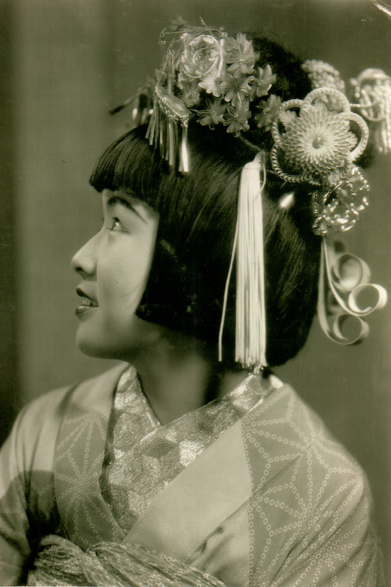 Young Sumako Hamaguchi with short black hair and decorative floral head piece