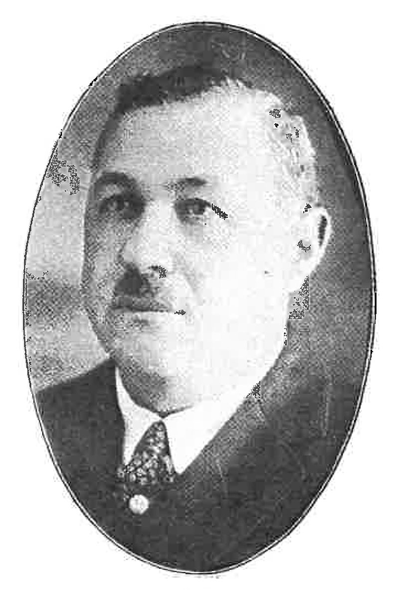Old oval-shaped black-and-white portrait of a man in a suit.