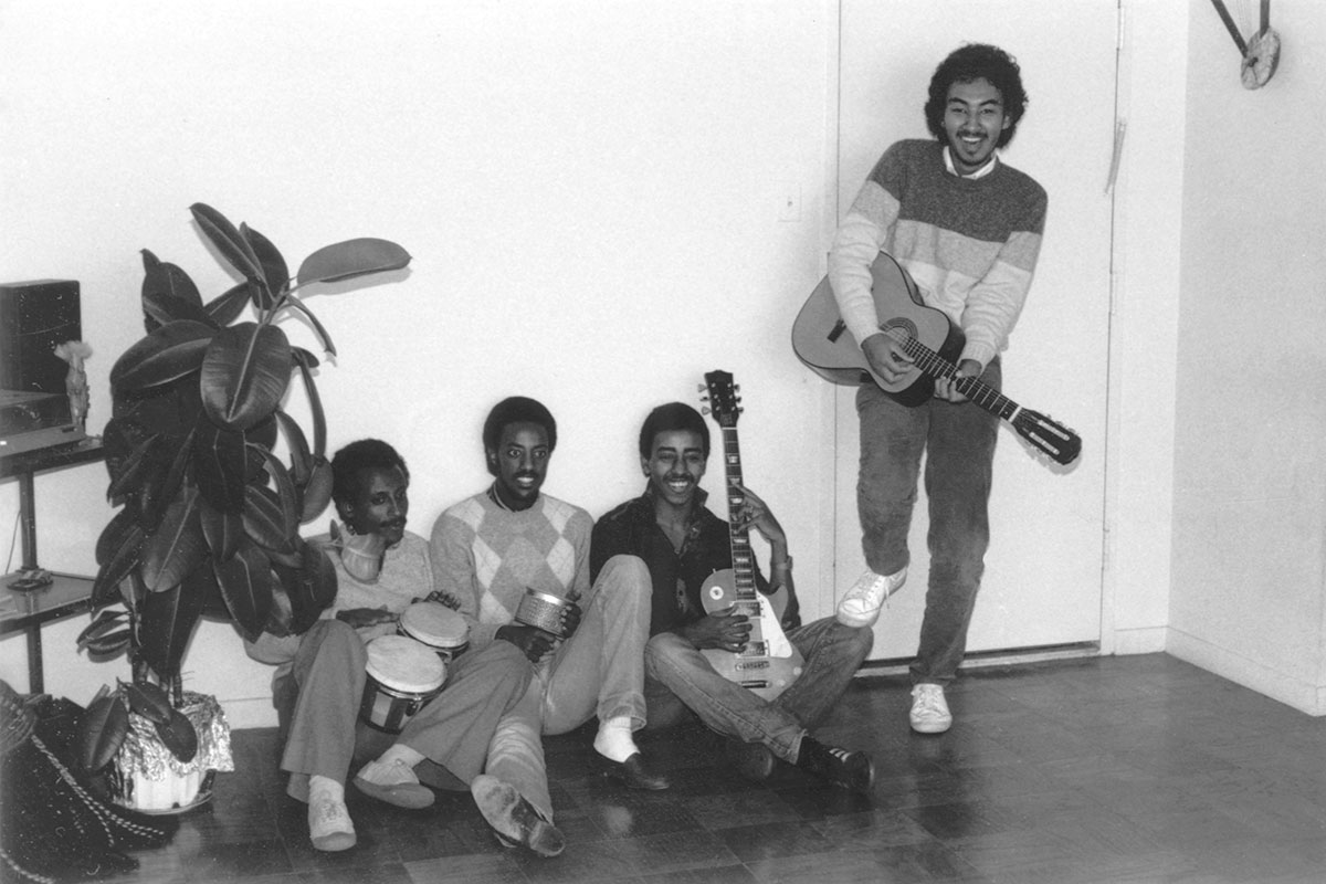Four men pose, three sitting on the ground with a house plant towering over them. They all hold instruments: bongos, a shaker, electric and acoustic guitars. Black-and-white photo.