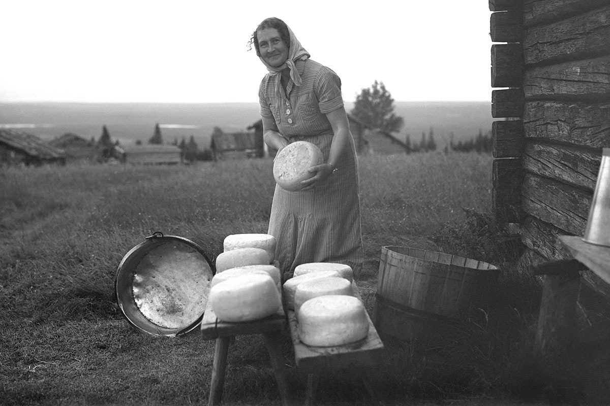 A woman stands among wheels of cheese set out to dry. Black and white photograph.