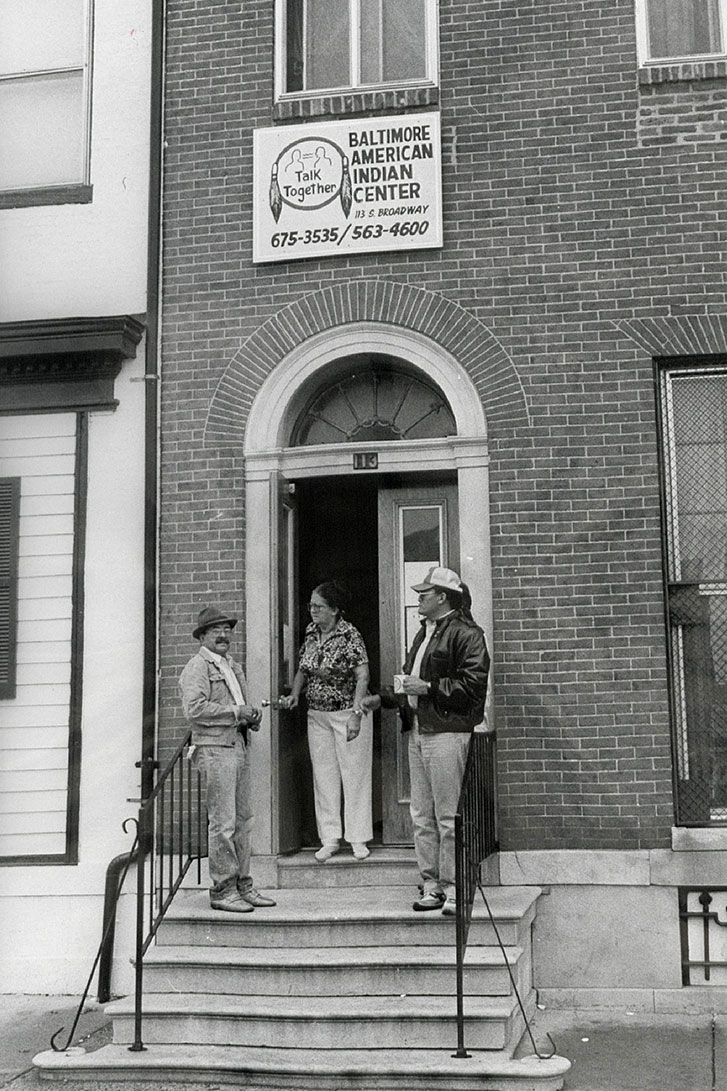 People gather on the front steps of a rowhouse building. A sign above the door reads: BALTIMORE AMERICAN INDIAN CENTER. Talk Together. With the address and phone number. Black-and-white photo.