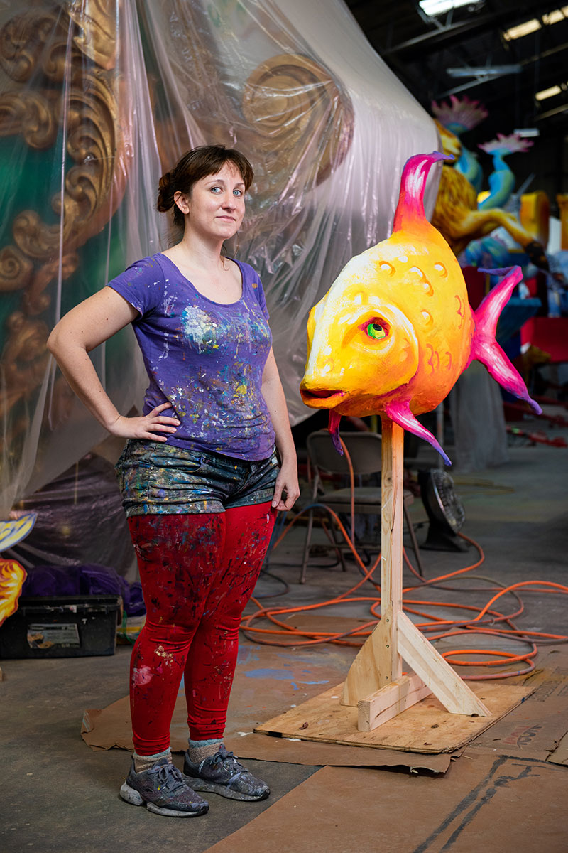 A woman with paint splattered all over her clothes poses next to a sculpture of a tropical fish, on a stand so it's as tall as her.