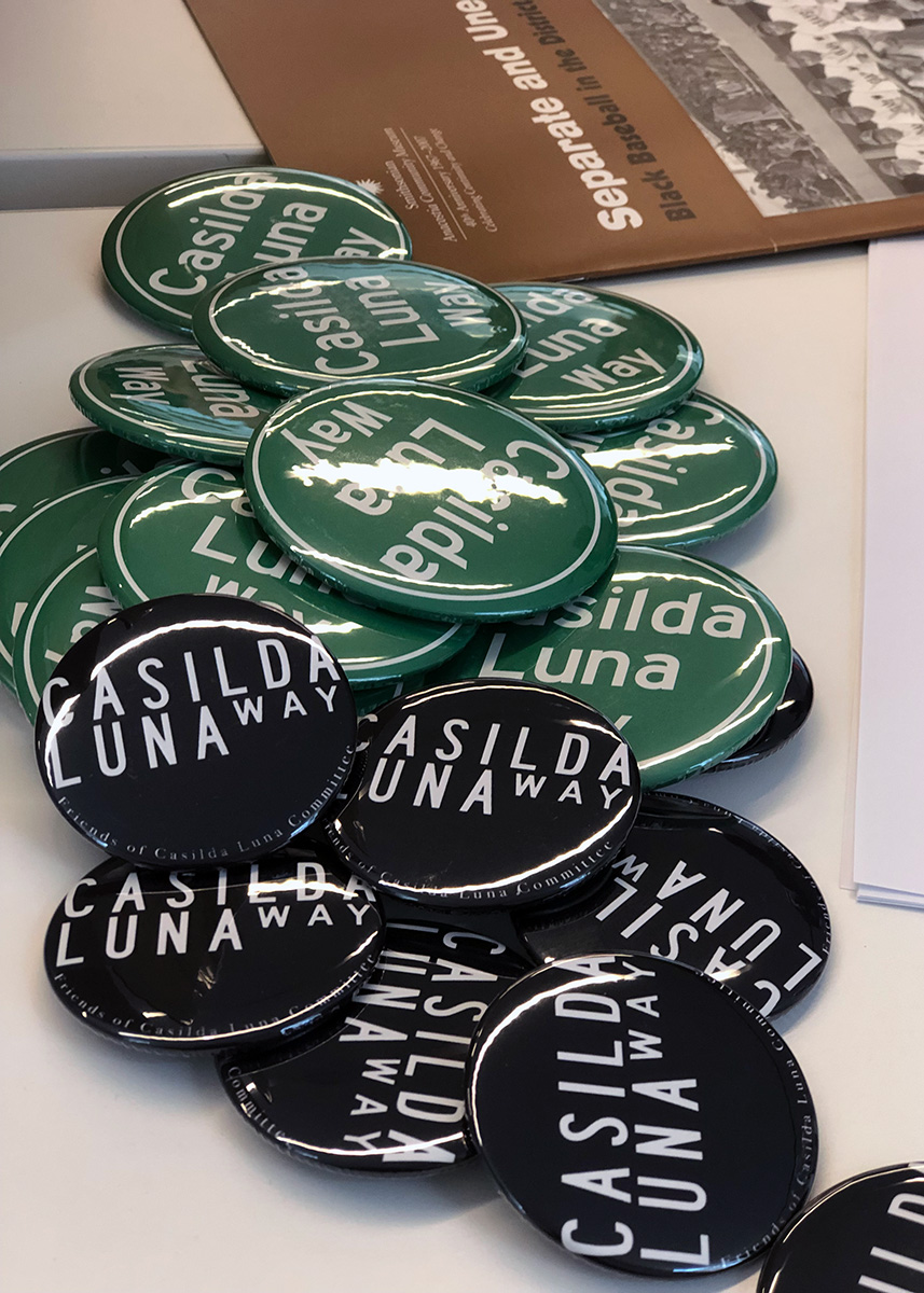 "Close-up of green and black campaign buttons reading ""Casilda Luna Way"""