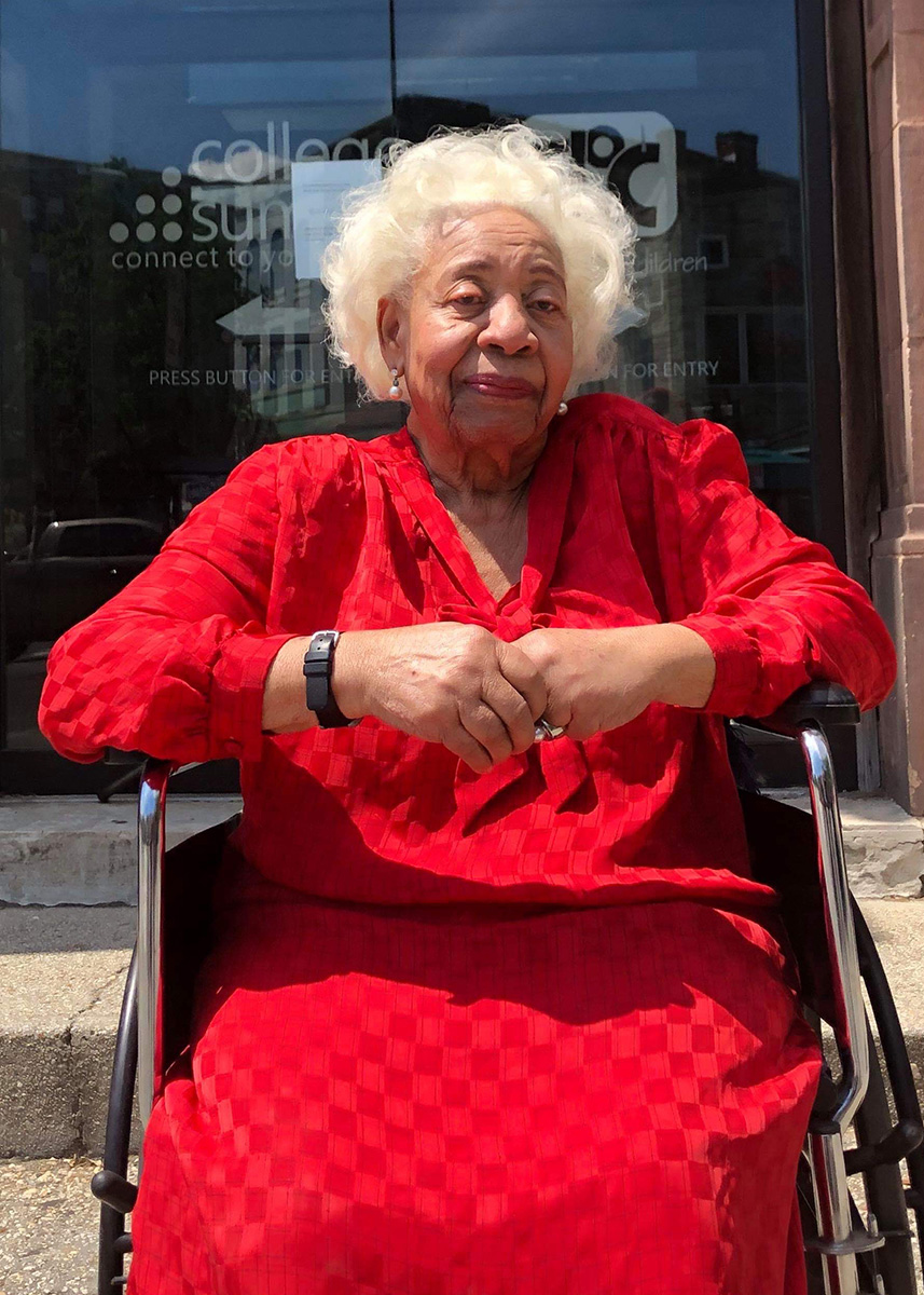 Casilda Luna with short white hair, bright red outfit, in a wheelchair
