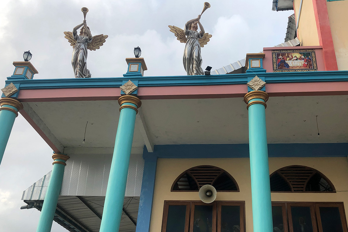 The exterior of a church shows pastel-colored columns and trim, with sculptures of two trumpeter angels on top of an awning. Above a window is a white loudspeaker pointed outward.