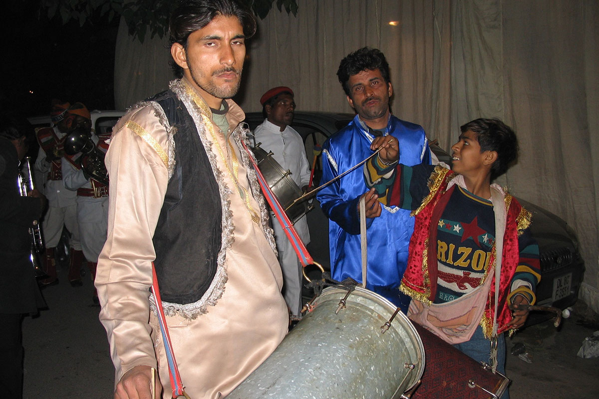 A nighttime wedding procession. A man in front carries a metal barrel-shaped drum over his shoulder and glares at the camera. Others in the background carry drums and brass instruments.