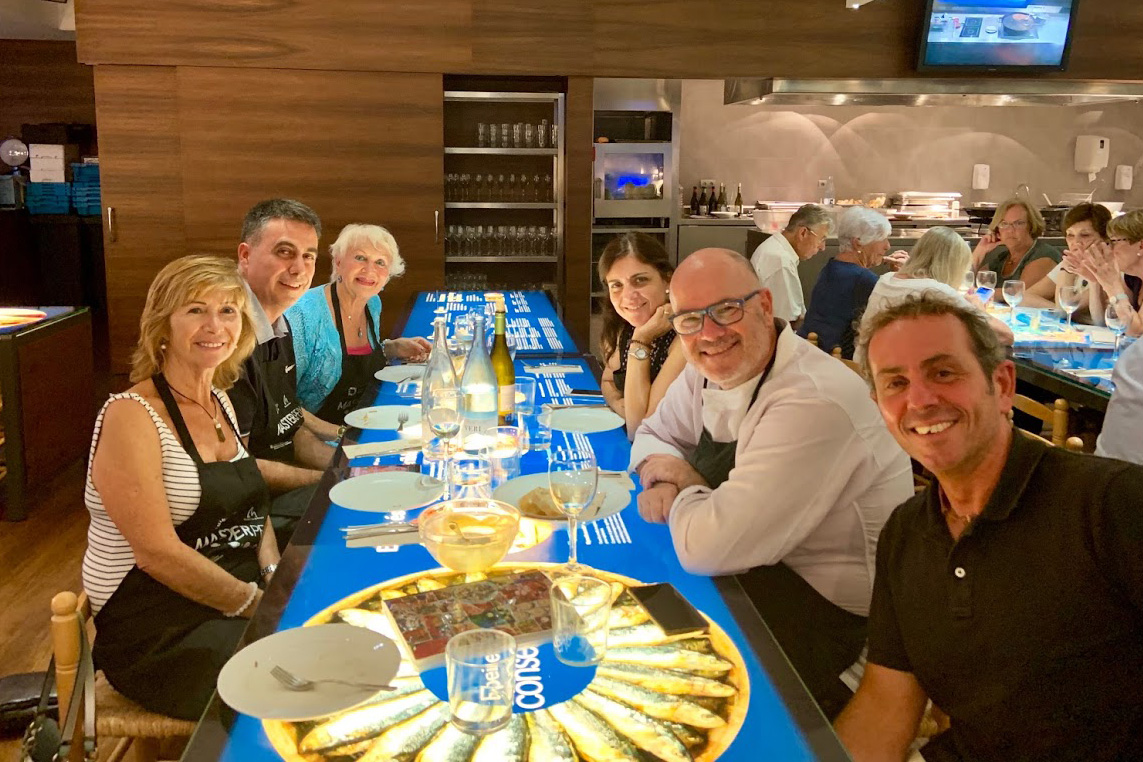 Six people smile for the camera, sitting at an illuminated table filled with plates and silverware, wine bottles and glasses.