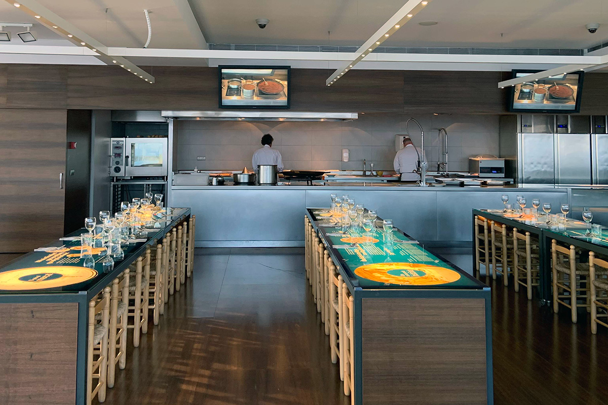 A kitchen tasting room includes rows of skinny tables with chairs neatly pushed in. At the back of the room is the kitchen, with two kitchen workers facing away from the camera.