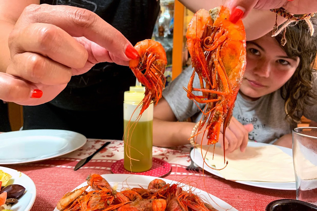In the foreground, two hands with red nail polish hold up two pieces of cooked shrimp, also bright red. Below is a plate full of shrimp and a squirt bottle full of oil or melted butter. In the corner, the face of a young woman eyes the shrimp.