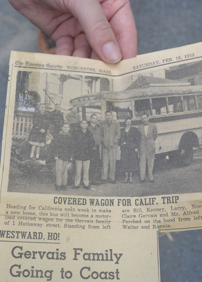 A hand holds up a newspaper clipping, showing a black-and-white photo of a large family posing in front of an on a bus. The headline reads: Gervais Family Going to Coast.