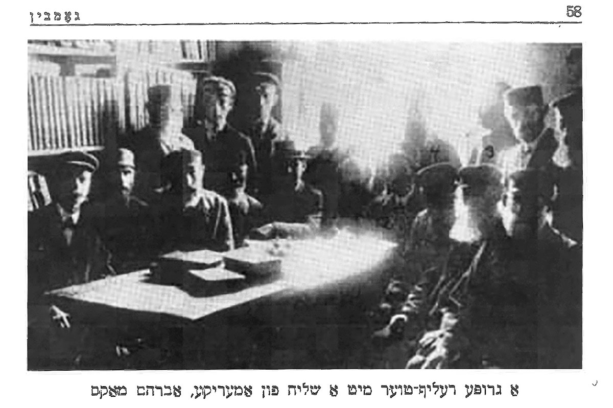 Old black-and-white portrait of a group of people sitting around a table. Printed caption is in Hebrew.