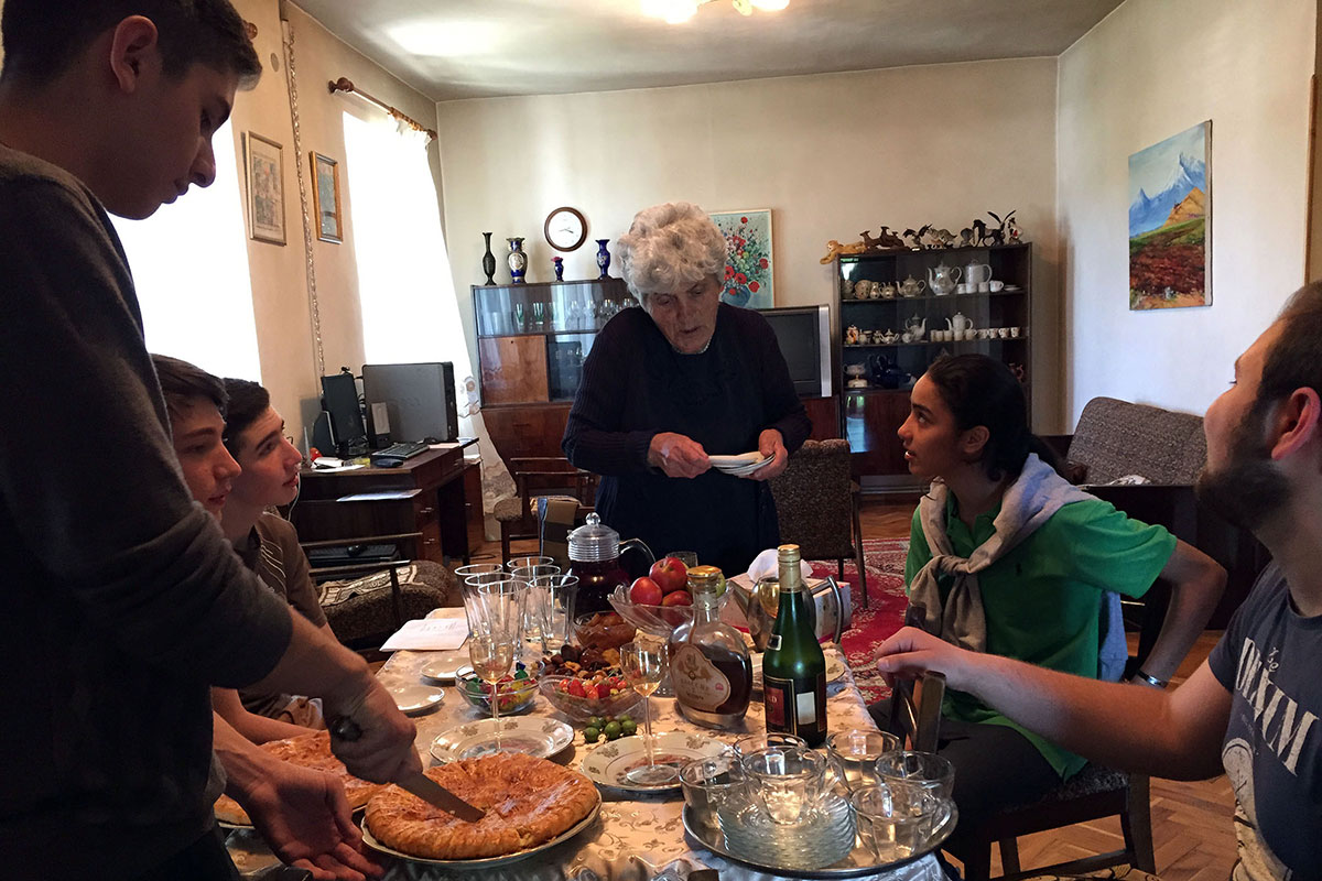 Older woman and teens talk around a table full of food and drink.