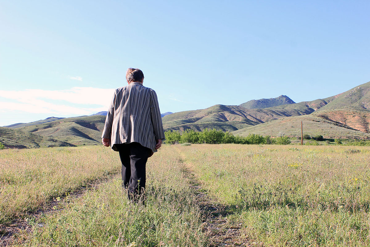 Older woman walks through a grassy field away from the camera, toward the mountains.