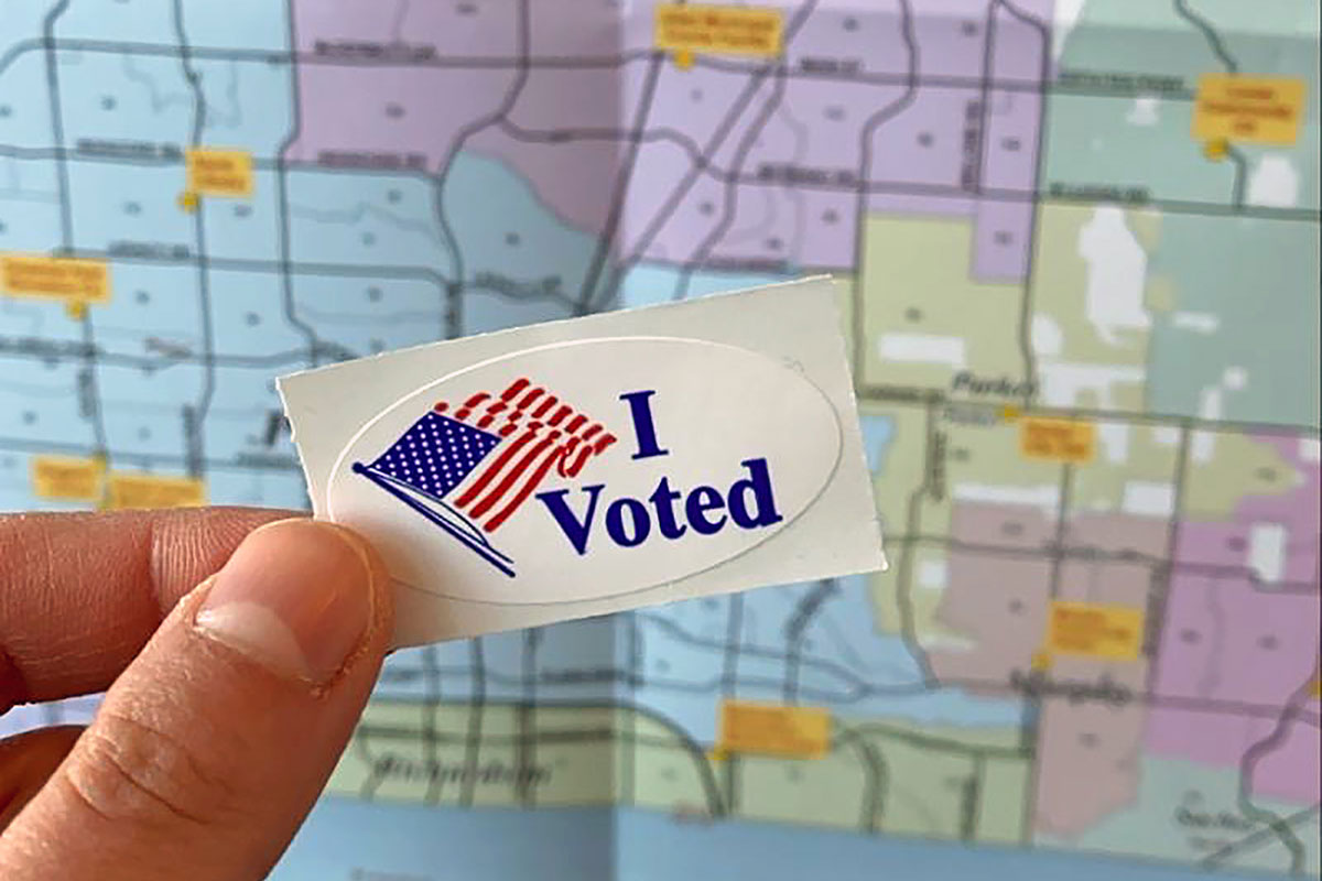 Close-up on a hand holding up an I Voted sticker in front of a map of Texas.