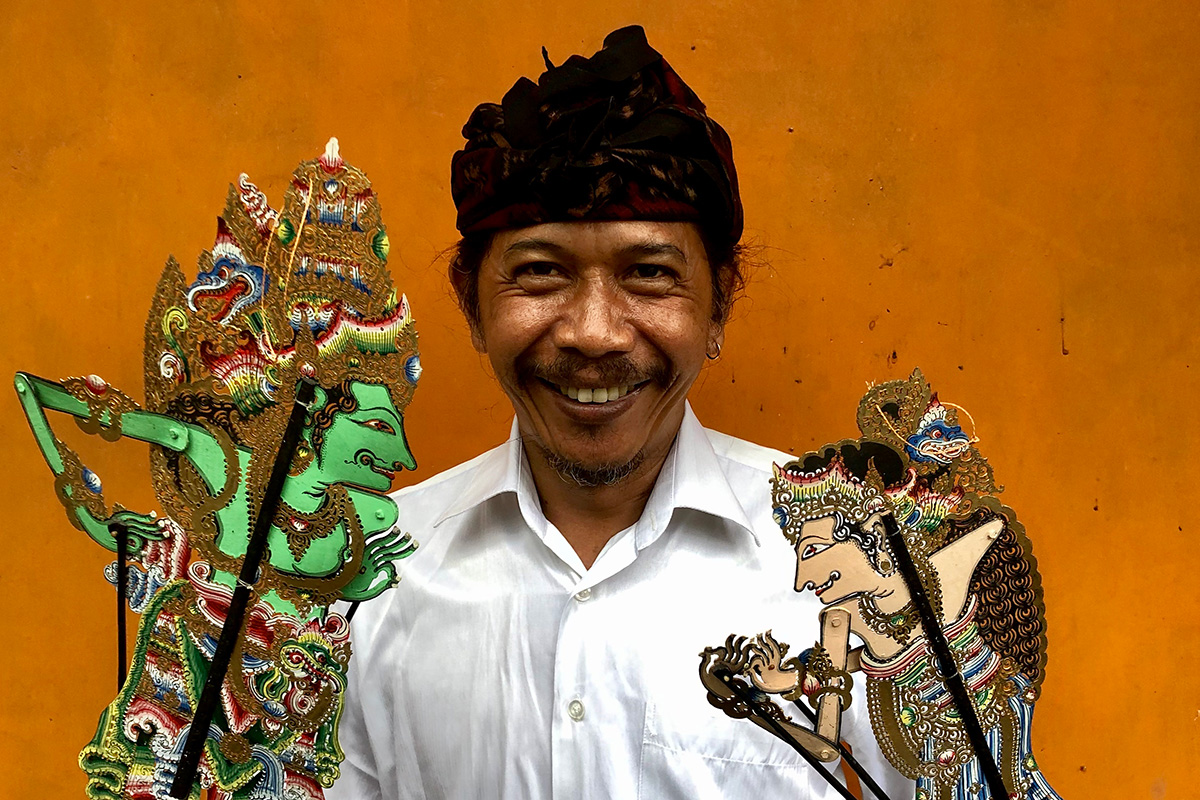 A man smiles at the camera, holding two intricately designed shadow puppets of human figures, controlled  by wooden sticks that run the length of their bodies. He wears a bright white dress shirt and traditional darkcolored peci headwrap.
