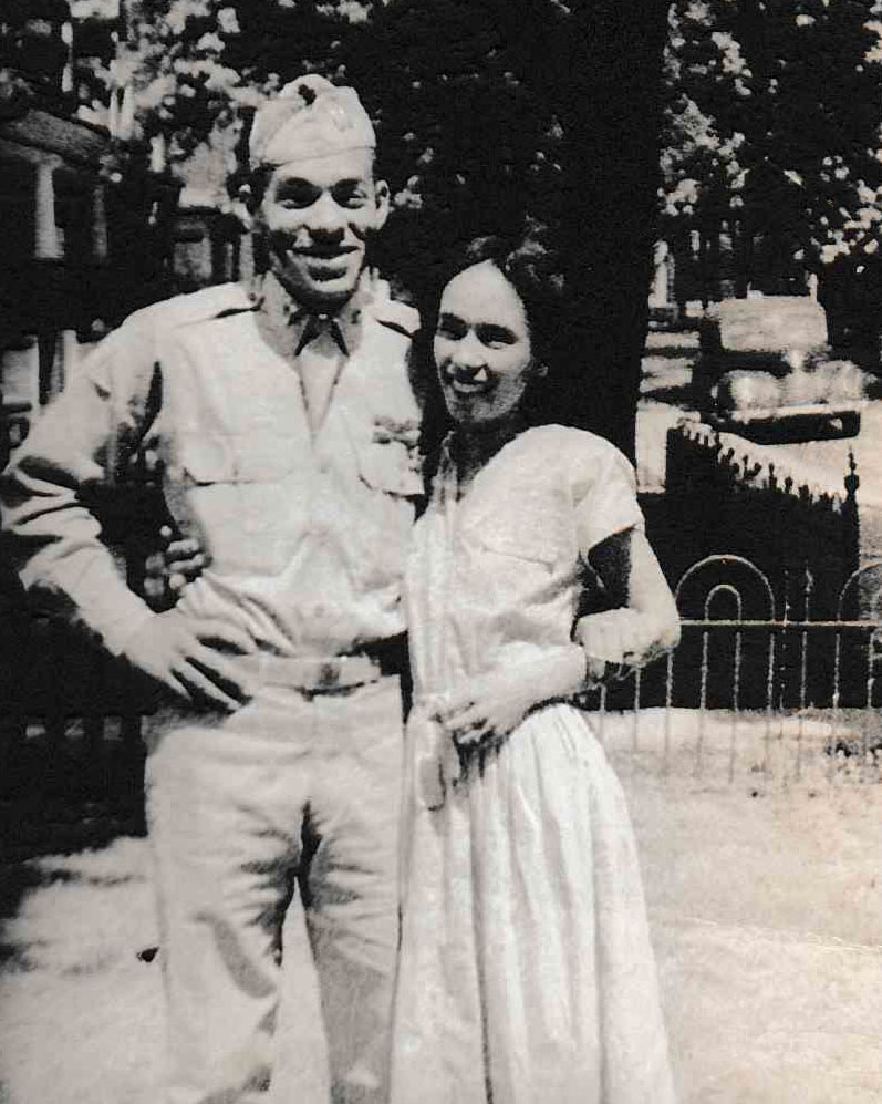 Black-and-white photo of a couple smiling, the man in uniform
