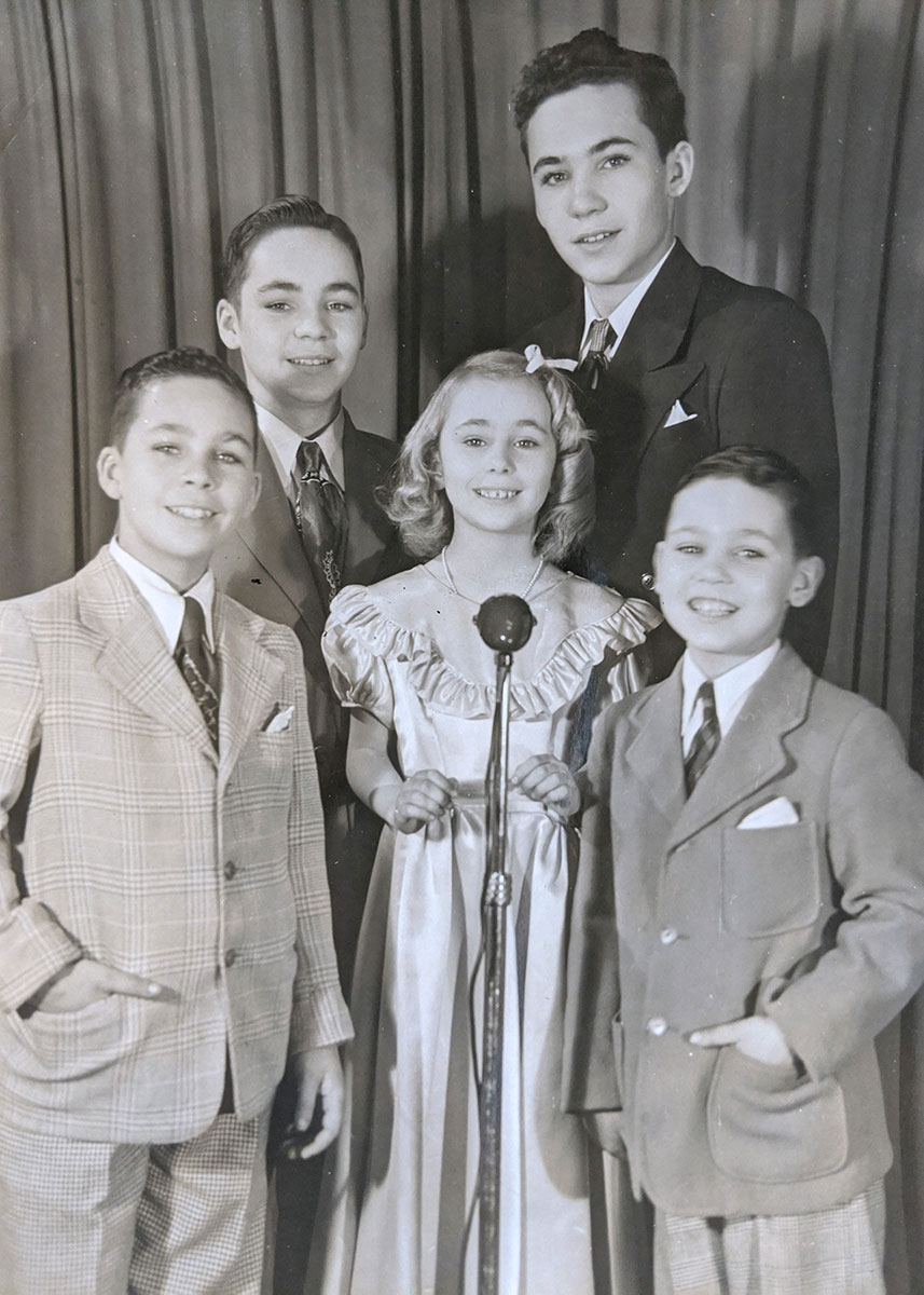 Five children, four boys and a girl, pose smiling in front of a microphone in formal wear.