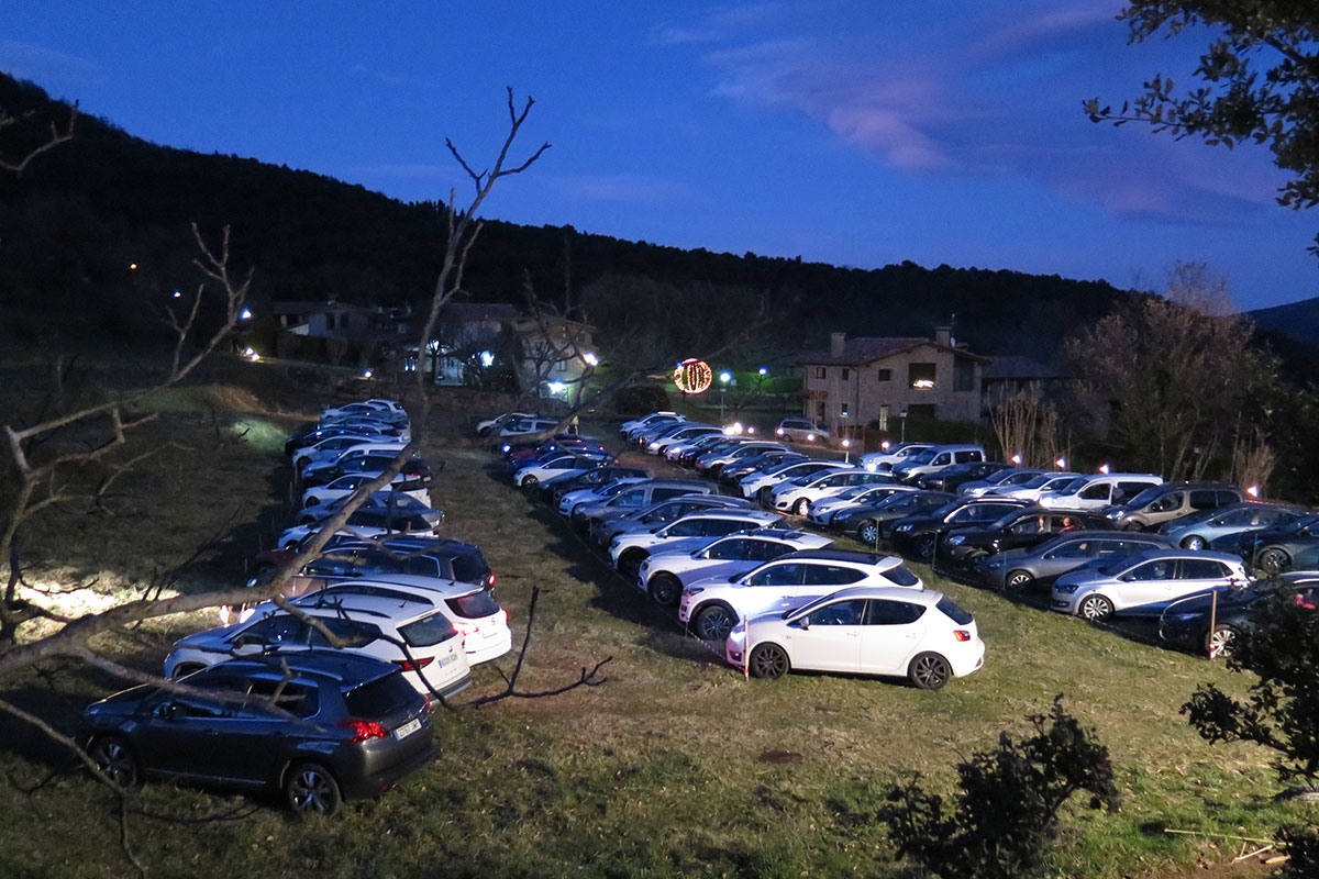 Rows of cars parked on a grassy field at dusk.