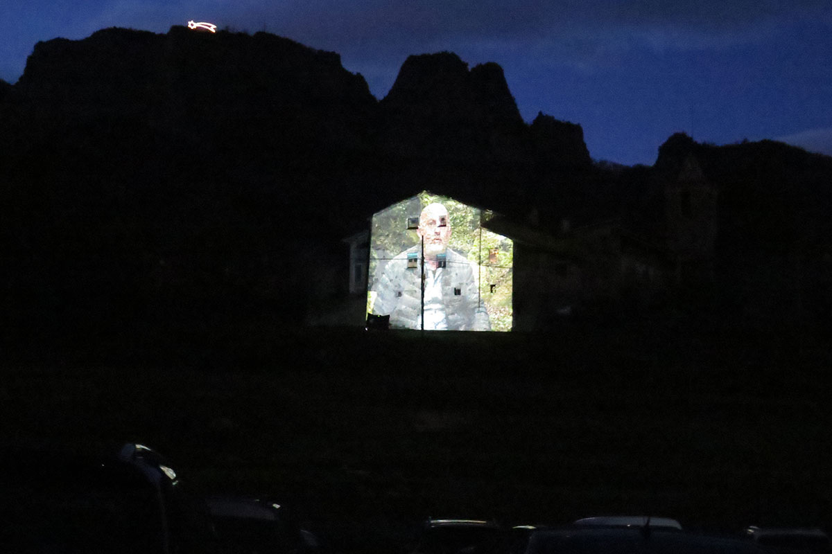 View from the parked cars: a projection of a man on the side of a church building. In the distance, an illuminated shooting star on the ridge of a mountain.