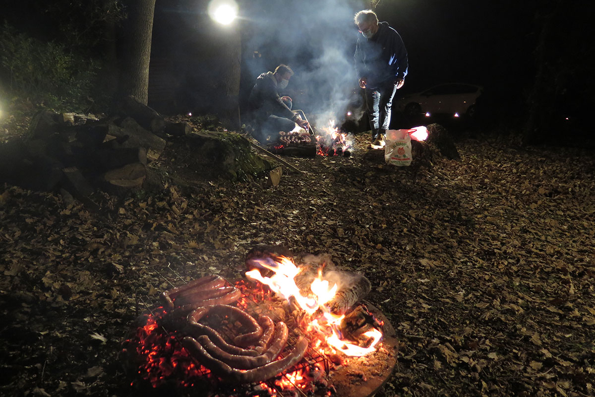 In the foreground, coils of sausage cooking on a firepit; in the background, two men tend another fire.