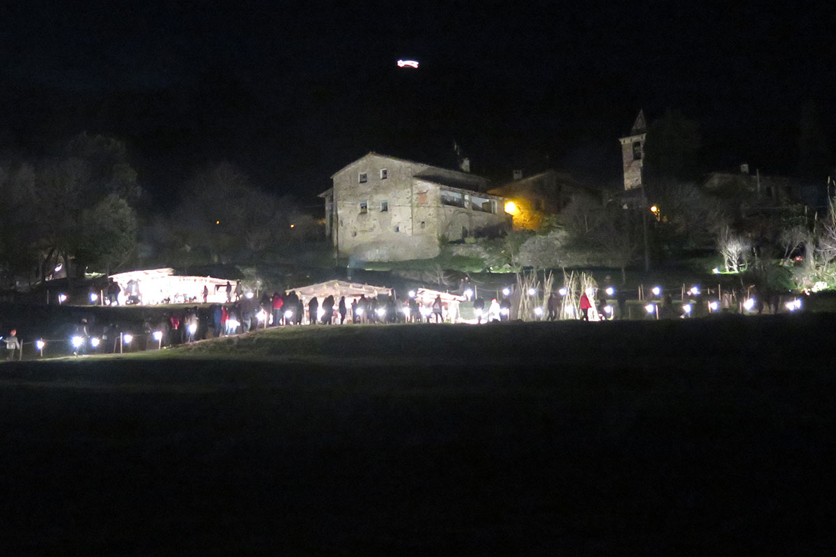 At night, a line of people holding lights in front of a church.