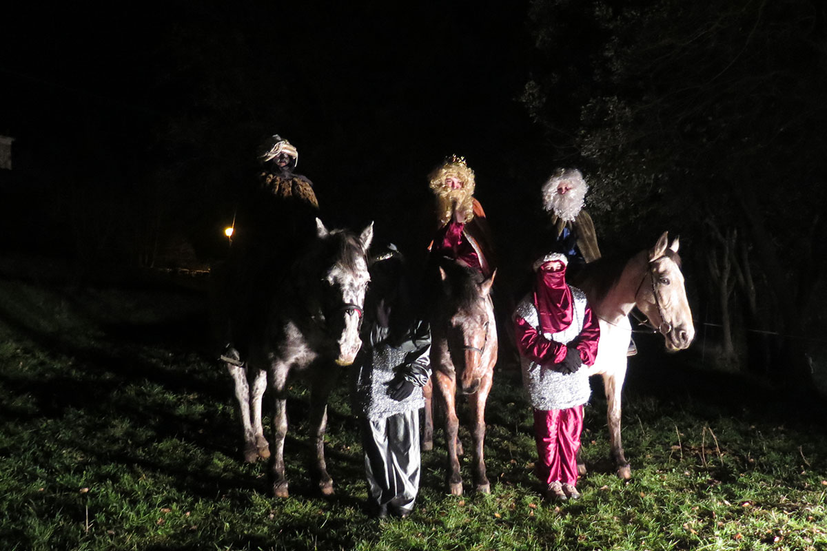 At night, three people on horses in wigs and beard, one in blackface, and two people standing between them.