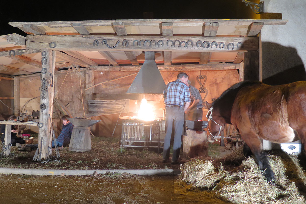 At night, men stand on either side of an anvil, next to a bright fire and rack of tools, under a row of horseshoes hung from a rafter. A horse watches them.