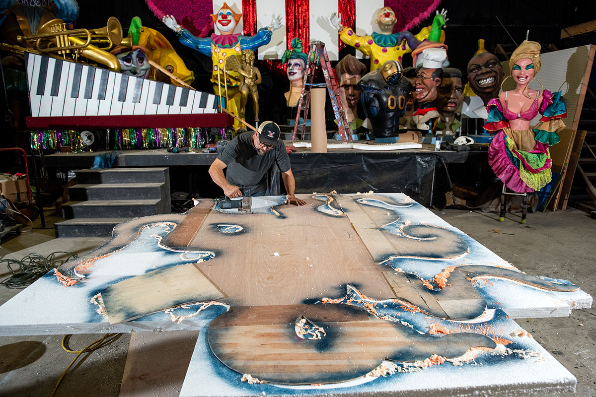 In a warehouse, a man works on painting a large prop piece on the ground. More colorful sculptural props are behind him, including piano keys and dancers.