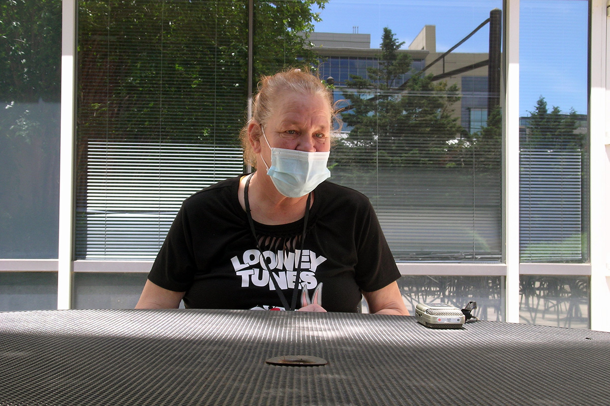Joni Metcalf stands across a metal grate from the photographer, wearing a mask and Looney Tunes T-shirt. An audio recorder for this interview is placed next to her.