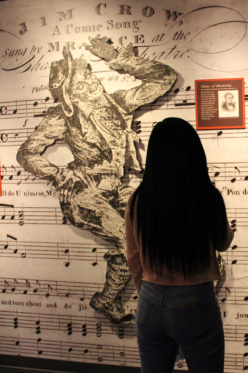 """A woman stands in front of a museum display, with blown-up sheet music of the song """"Jump Jim Crow"""" and a cartoon of the title character."""