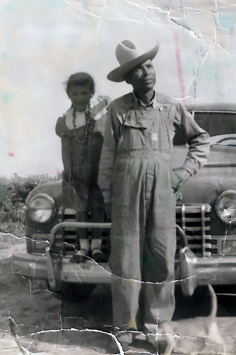 A young girl stands on the fender of an old truck alongside her father in overalls and cowboy hat. The black-and-white photo has been crinkled and stained.