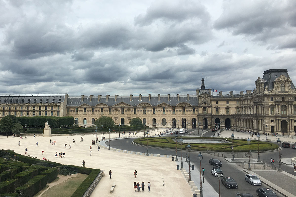 Wide shot of the Louvre and the plaza in front, with only sparse groups of people walking on the pathway.