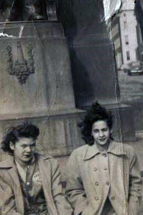 Two women in trenchcoats pose on a city street on what appears a very windy day. Black-and-white photo.
