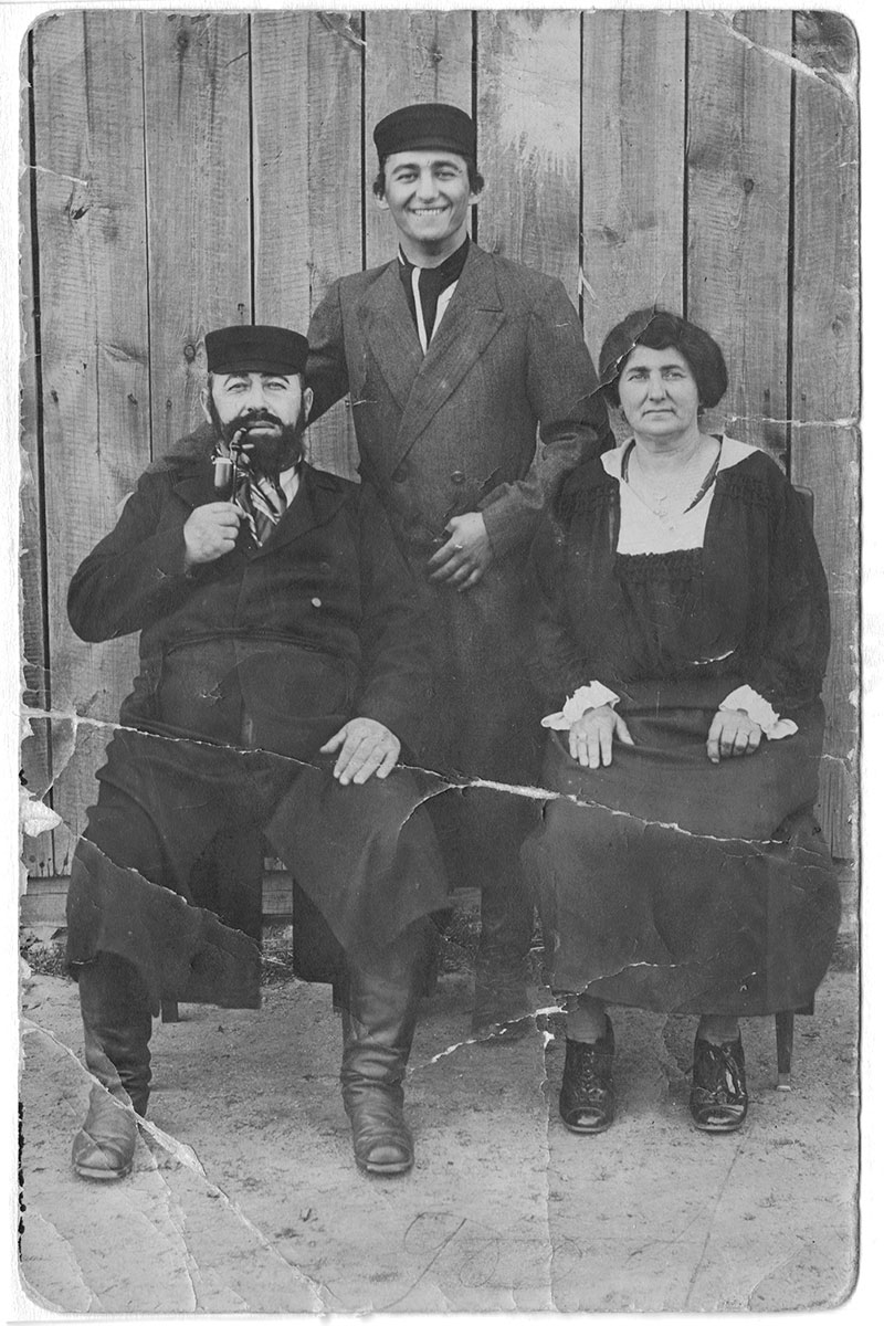 Old black-and-white photo of parents and son.