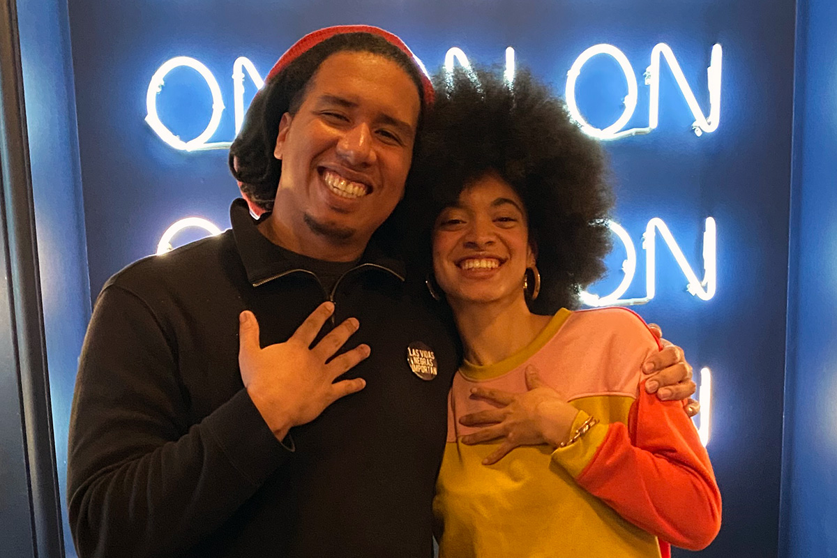 "Manny Mendez and Gyselle Garcia pose in their podcast studio, with neon lights behind them reading ""ON ON ON ON ON ON"""