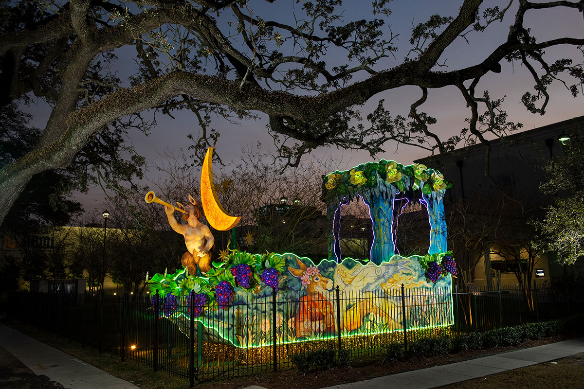 A yard decorated with a forest scene: animals, foliage, and a mythical creature sounding a trumpet under a yellow crescent moon. At night, the edges of the sculpture are lit up in green.