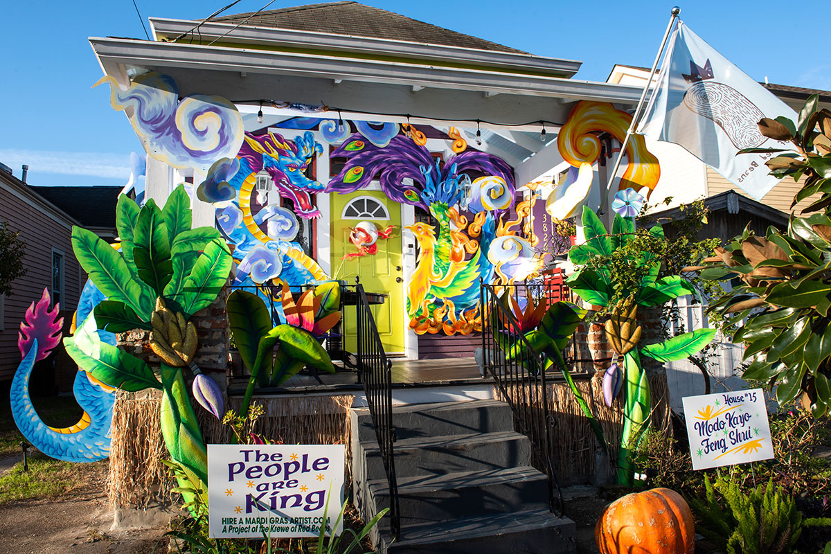 Exterior ofa house decorated with sculptural dragon, palm trees, and other mythical creatures. A lawn sign in front reads THE PEOPLE ARE KING.