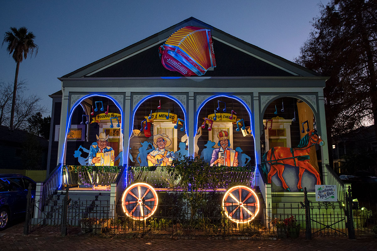 After dark, a porch with four arches decorated to look like a wagon, pulled by a two-dimensional horse in the stairway entrance, and three figures playing instruments under the arches. A giant lit-up accordion sculpture hanging at the apex of the A-frame house.