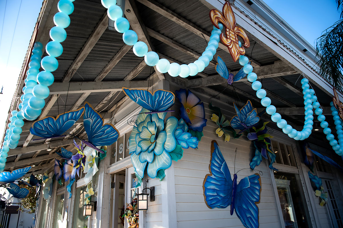 Exterior of a house decorated with giant blue butterflies and blue pearl-like streamers.