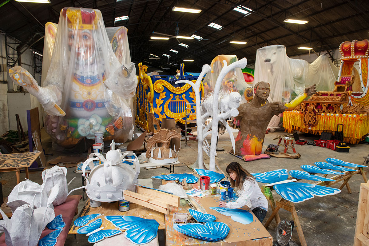 In a warehouse, a woman paints prop pieces on the ground, with several other float pieces behind her.