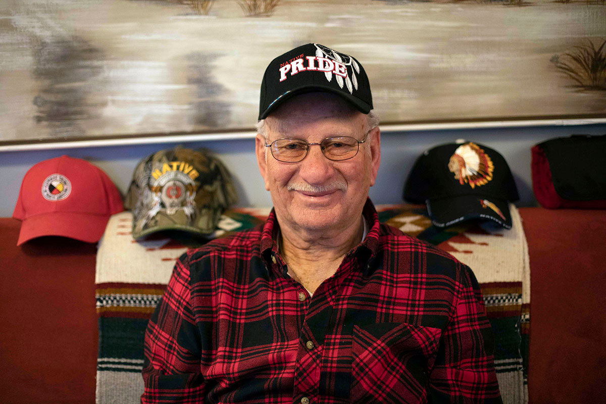 An elderly man smiles for the camera, wearing a baseball cap that reads NATIVE PRIDE.