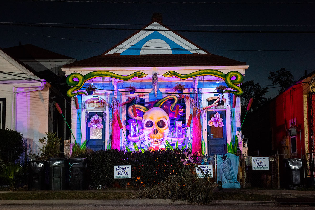 After dark, exterior of a house lit up in purple, with a large human skull sculpture hanging on front. Below the eave of the house are two large painted snakes.