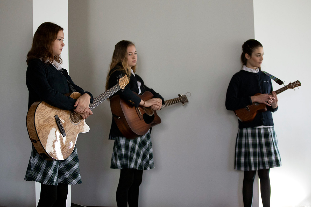 Three young men stand blankly in a hallway, looking like they are waiting for direction. Two hols acoustic guitars and the third a ukulele. They all wear matching school uniforms: navy sweaters, white collared shirts, plaid skirts, and black stockings.