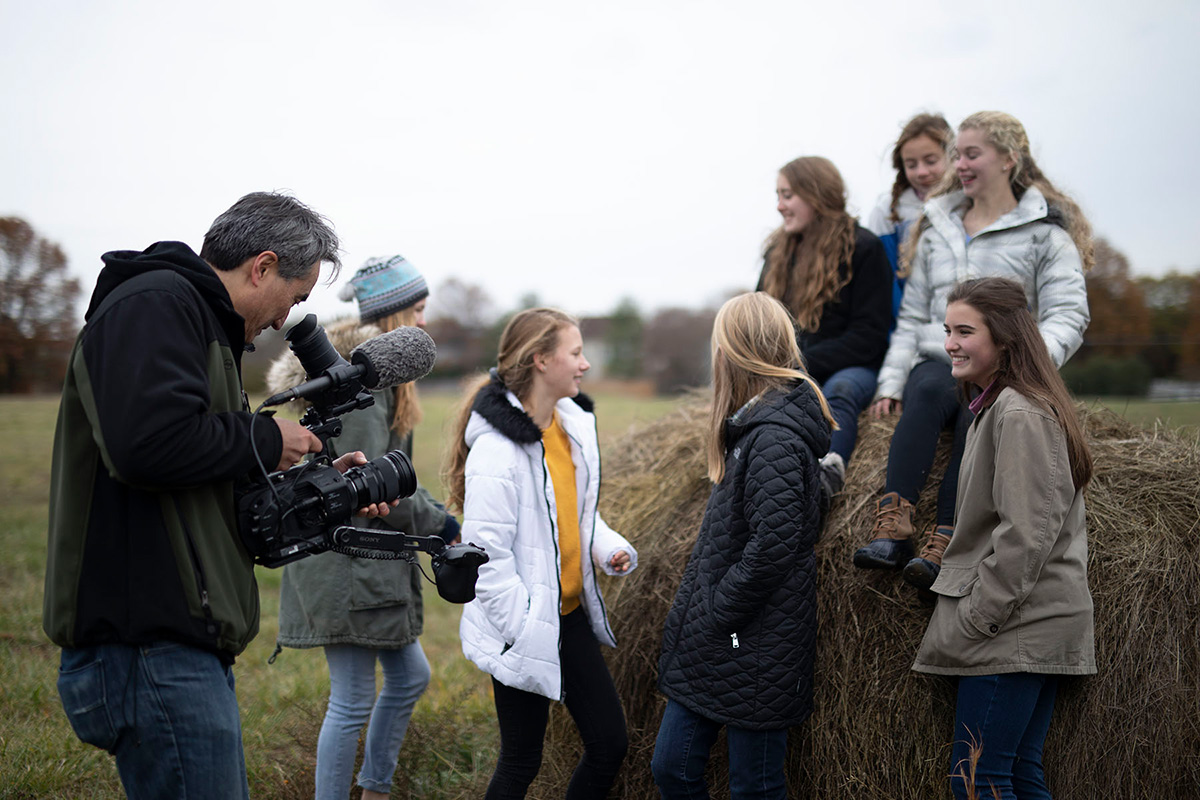 A man (the author) on the left looks into the viewfinder of a video camera, filming a group of seven chorus members chatting on and around a haystack. They are all dressed in warm jackets, lit by a bright but overcast sky.