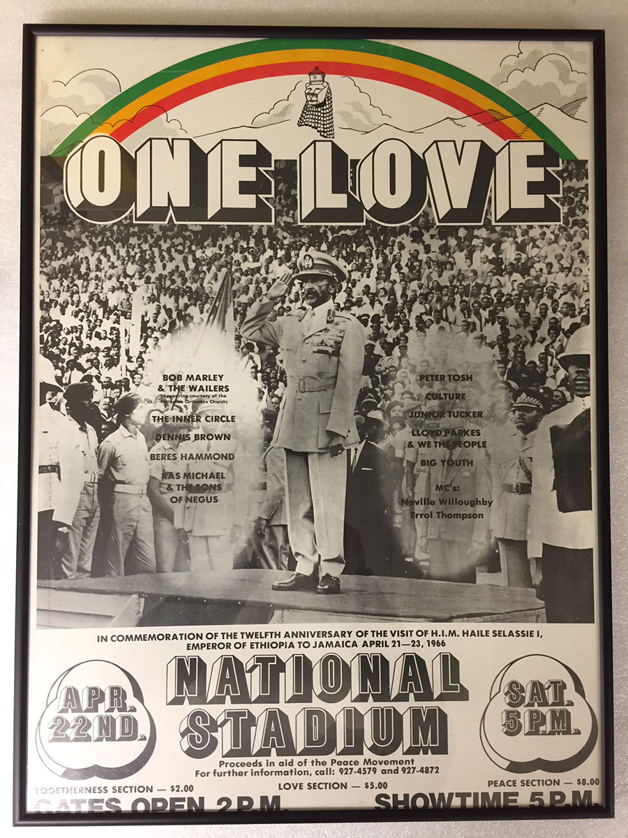 Old concert poster with Emperor Haile Selassie in front of a crowd, with the words ONE LOVE, at National Stadium, with a rainbow of red, yellow, and green.