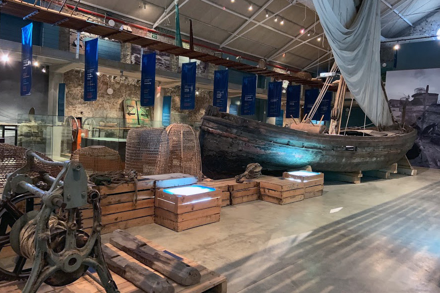 A large, dark room in a museum shows all kinds of fishing gear, woven fish nets, and a wooden boat with canvas mast. Informational screens set in wooden pallet cases are illuminated in blue.