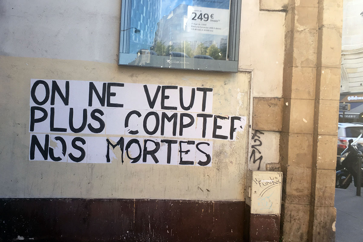 Black words graffitied on a wall on the street in French: On ne veut plus compter nos mortes.