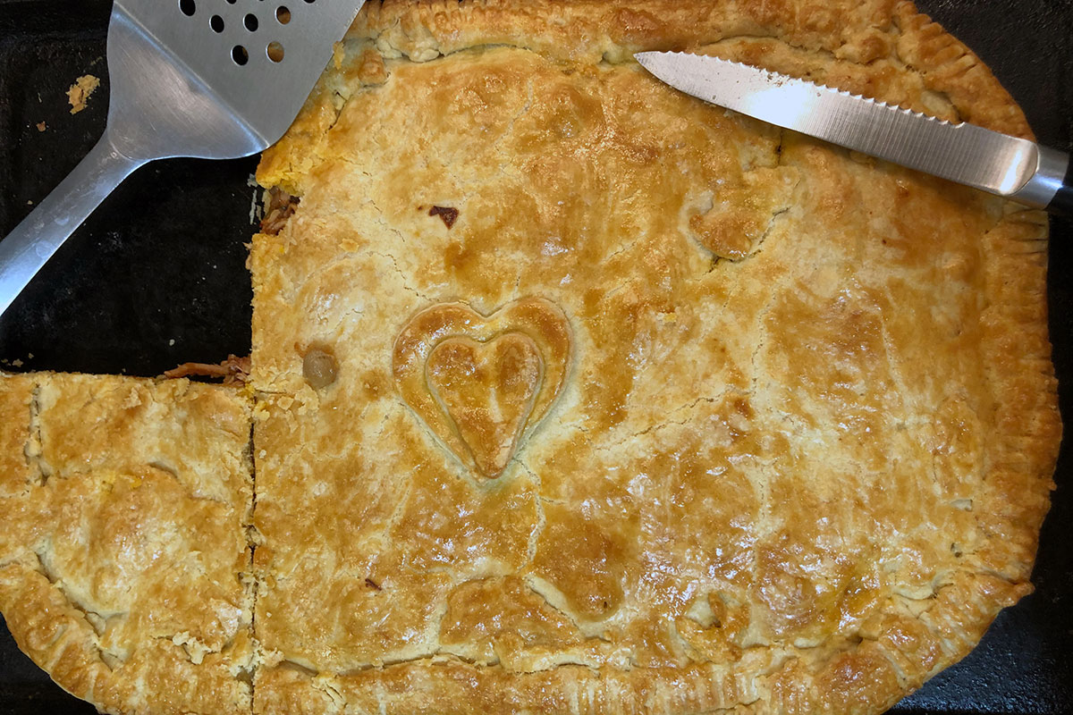 Rectangular pie with a slice cut out, and two heart shapes on top.