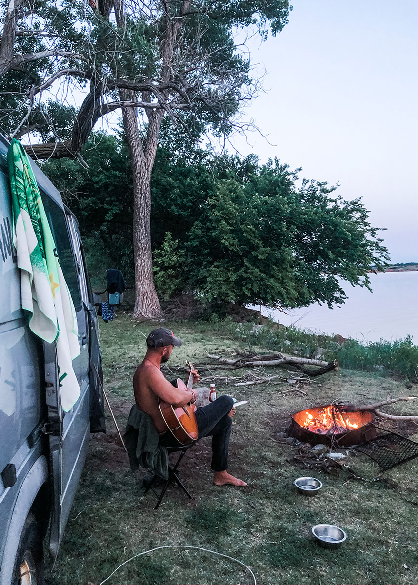 A man strums an acoustic guitar, sitting between a large van and a burning fire pit at the side of a lake.